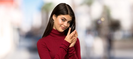 Teenager girl with turtleneck scheming something at outdoors