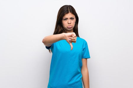 Teenager girl with blue shirt showing thumb down with negative expression