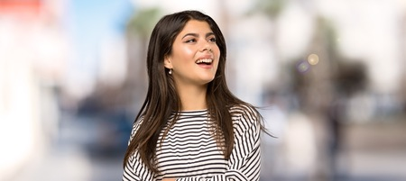 Teenager girl with striped shirt looking up while smiling at outdoors