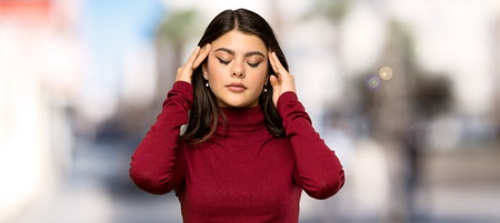 Teenager girl with turtleneck with headache at outdoors