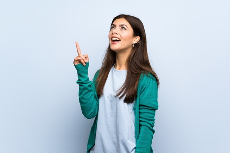 Teenager girl over blue wall intending to realizes the solution while lifting a finger up