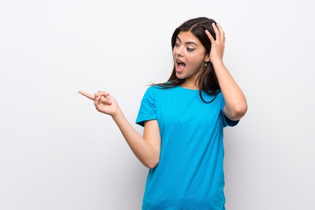 Teenager girl with blue shirt surprised and pointing finger to the side