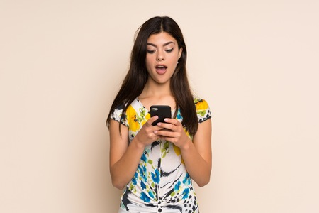 Teenager girl with floral dress surprised and sending a message