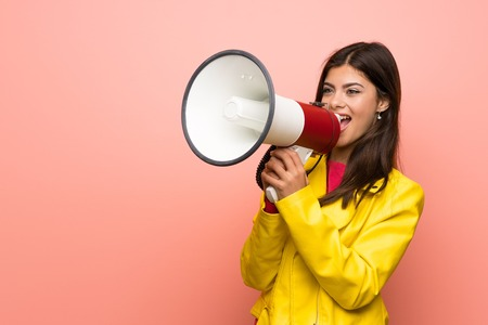 Teenager girl over pink wall shouting through a megaphone