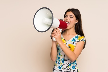 Teenager girl with floral dress shouting through a megaphone