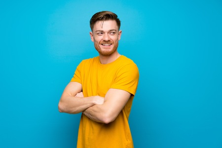 Redhead man over blue wall with arms crossed and happy