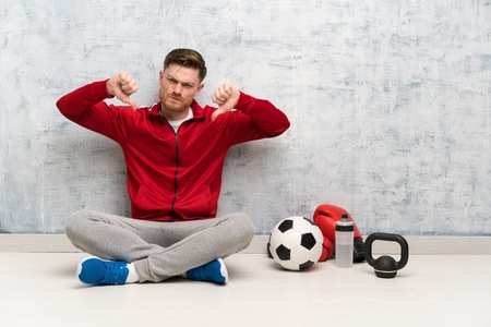 Redhead sport man showing thumb down