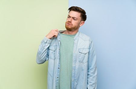 Redhead man over colorful background with tired and sick expression