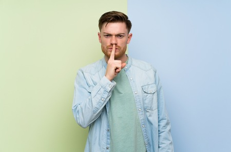 Redhead man over colorful background showing a sign of silence gesture putting finger in mouth