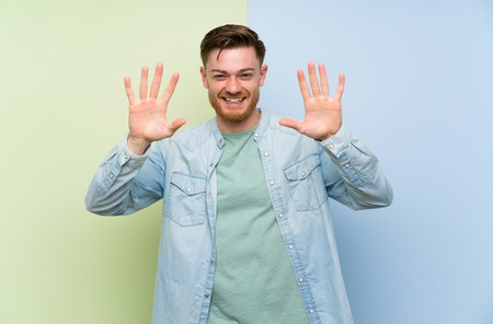 Redhead man over colorful background counting ten with fingers