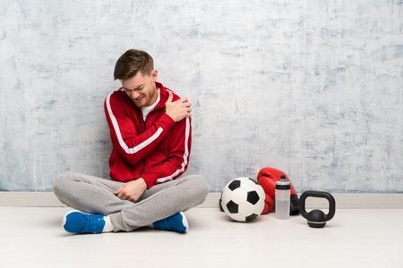 Redhead sport man suffering from pain in shoulder for having made an effort Reklamní fotografie