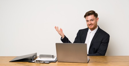Businessman in a office extending hands to the side for inviting to come Stock Photo