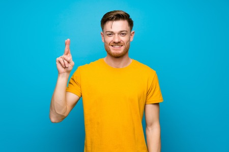 Redhead man over blue wall with fingers crossing and wishing the best