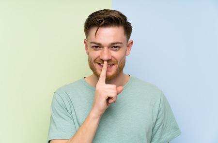 Redhead man over colorful background doing silence gesture 版權商用圖片