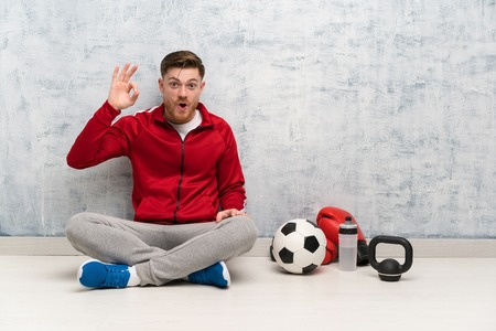 Redhead sport man surprised and showing ok sign Imagens