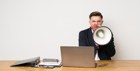 Businessman in a office shouting through a megaphone