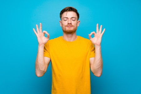 Redhead man over blue wall in zen pose