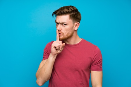 Redhead man on isolated blue wall doing silence gesture