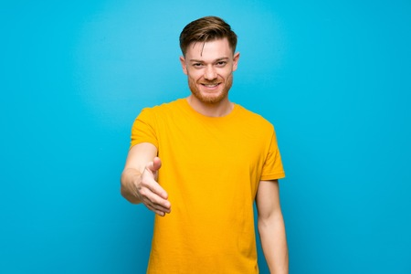 Redhead man over blue wall shaking hands for closing a good deal