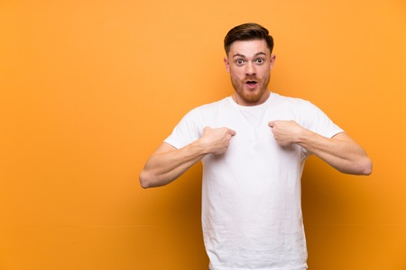 Redhead man over brown wall with surprise facial expression 免版税图像