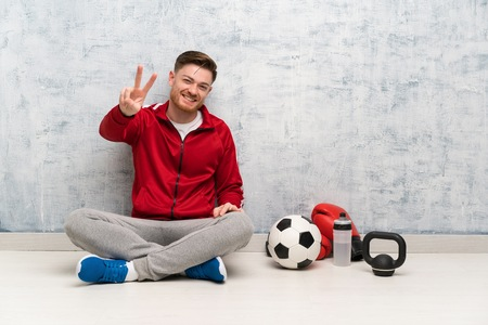 Redhead sport man smiling and showing victory sign
