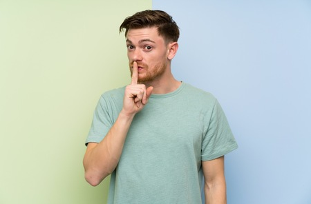 Redhead man over colorful background doing silence gesture Stock Photo
