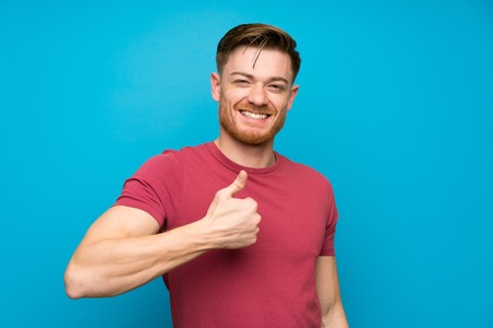 Redhead man on isolated blue wall giving a thumbs up gesture