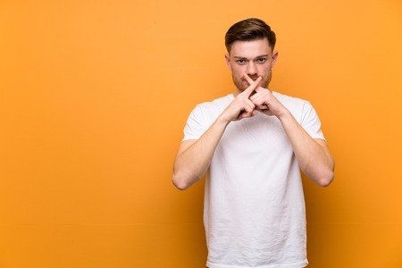 Redhead man over brown wall showing a sign of silence gesture