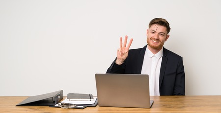 Businessman in a office happy and counting three with fingers Banco de Imagens