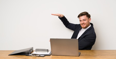 Businessman in a office holding copyspace to insert an ad