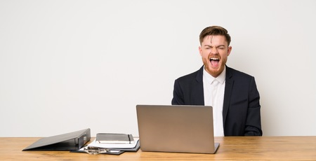 Businessman in a office shouting to the front with mouth wide open 免版税图像