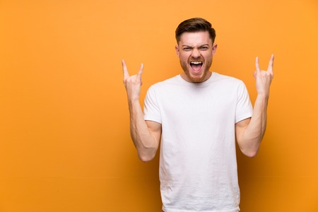 Redhead man over brown wall making rock gesture Stock Photo