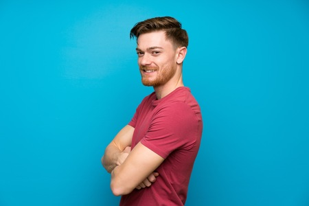 Redhead man on isolated blue wall laughing