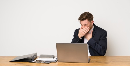 Businessman in a office is suffering with cough and feeling bad 免版税图像