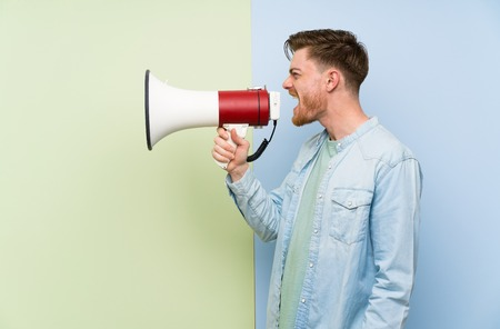 Redhead man over colorful background shouting through a megaphone