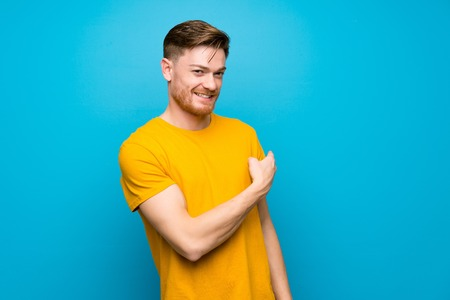 Redhead man over blue wall pointing back