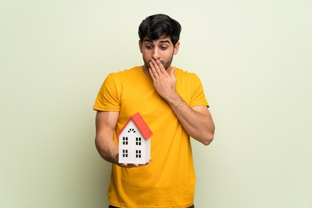 Young man over pink wall holding a little house Stock Photo