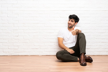 Young man sitting on the floor with thumbs up because something good has happened Stock Photo