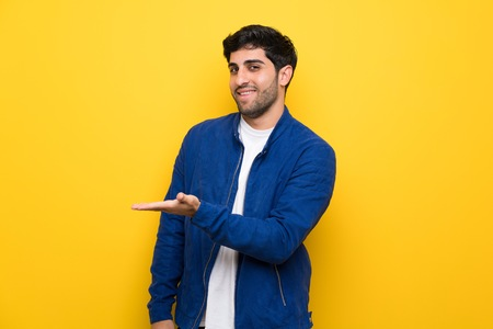 Man with blue jacket over yellow wall presenting an idea while looking smiling towards
