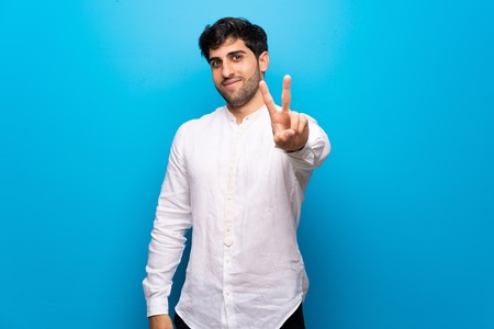Young man over isolated blue wall smiling and showing victory sign Stock Photo