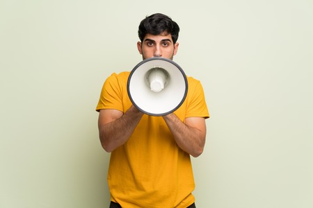 Young man over pink wall shouting through a megaphone