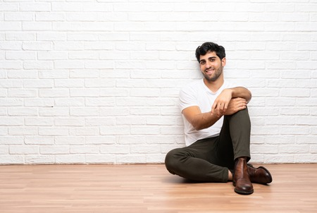 Young man sitting on the floor laughing