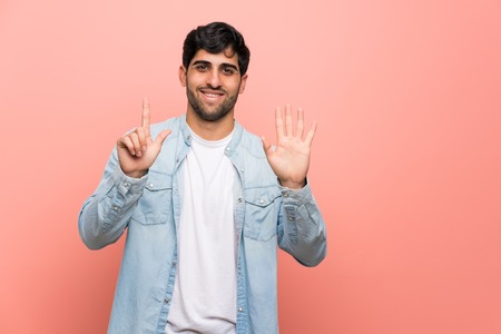 Young man over pink wall counting seven with fingers Stock Photo