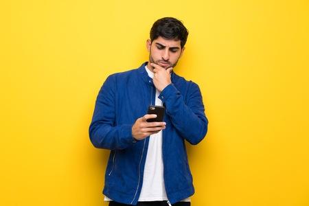 Homme avec une veste bleue sur un mur jaune pensant et envoyant un message