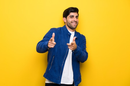 Man with blue jacket over yellow wall pointing to the front and smiling Stock Photo