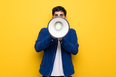 Man with blue jacket over yellow wall shouting through a megaphone