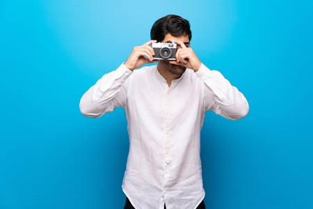 Young man over isolated blue wall holding a camera