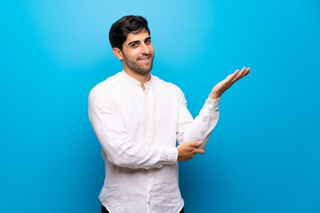 Young man over isolated blue wall extending hands to the side for inviting to come Stock Photo