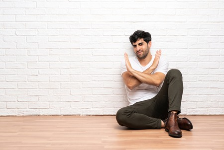 Young man sitting on the floor making NO gesture