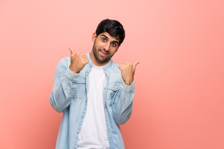 Young man over pink wall with thumbs up gesture and smiling
